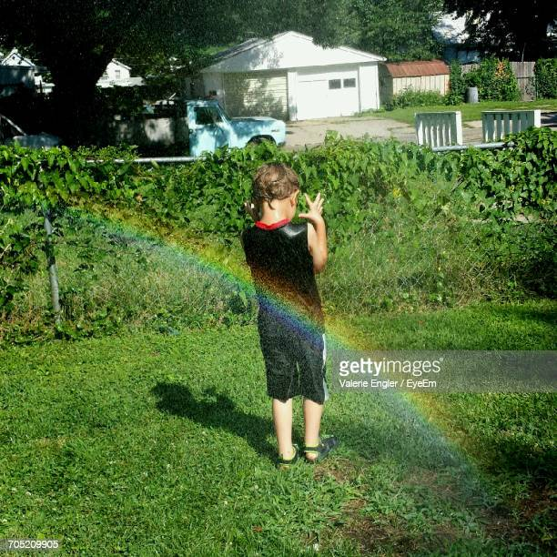 Rainbow By Wet Boy Standing In Back Yard
