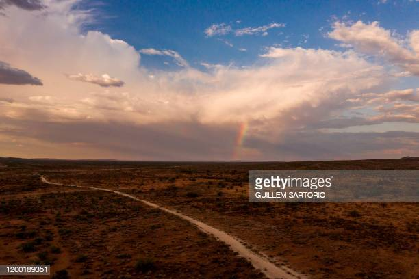 A rainbow can be seen crossing the sky in the northern Kalahari region near Groblershoop on January 15 2020 In the Northern Cape Province of South...