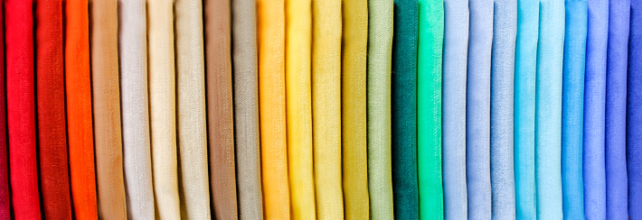Rainbow clothes background. Pile of bright folded clothes. 922685294