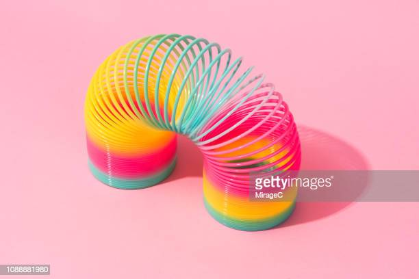 rainbow coil toy - metal coil toy stock photos and pictures