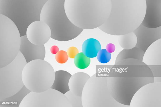 rainbow color spheres against monochrome spheres - isolated color stock pictures, royalty-free photos & images