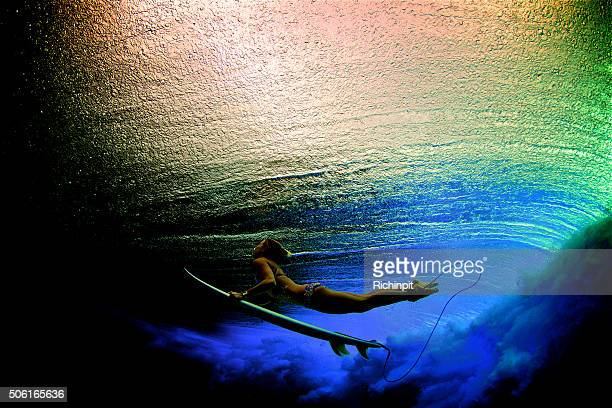 Rainbow colored duck dive of surfer girl