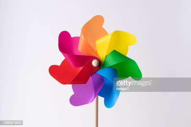 rainbow colored pinwheel toy - paper windmill stock photos and pictures