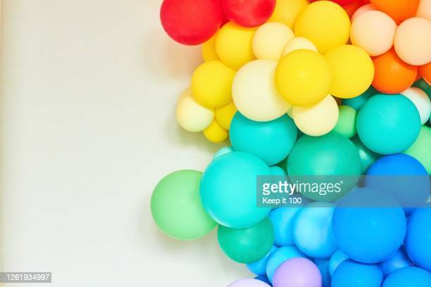 a rainbow coloured collection of balloons - celebratory event stock pictures, royalty-free photos & images