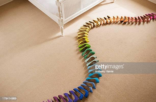 Rainbow coloured shoes in line on bedroom floor