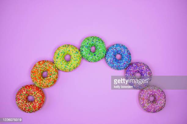 rainbow doughnuts sweets on purple background with copy space - cake stock pictures, royalty-free photos & images