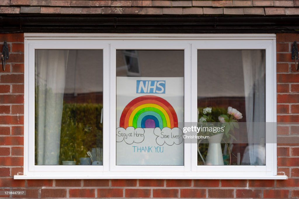 Rainbow drawings in window of house during Covid19 in UK. : Stock Photo