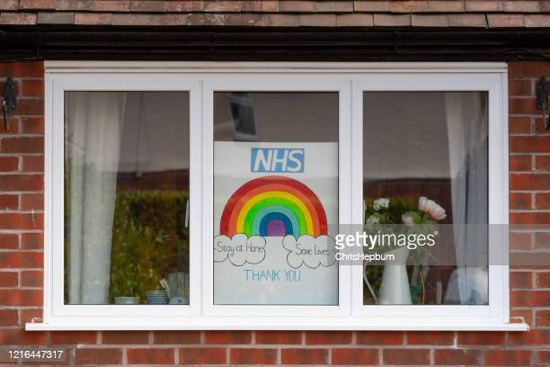 rainbow drawings in window of house during covid19 in uk. - rainbow stock pictures, royalty-free photos & images