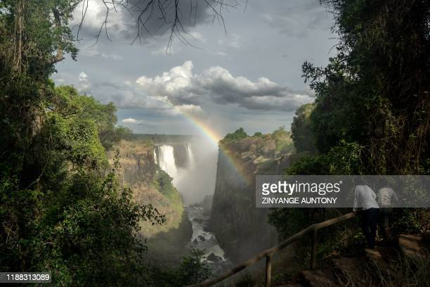 TOPSHOT A rainbow emerges at the majestic Victoria Falls a tourism attraction for on December 10 2019 The Victoria Falls a UNESCO world heritage site...