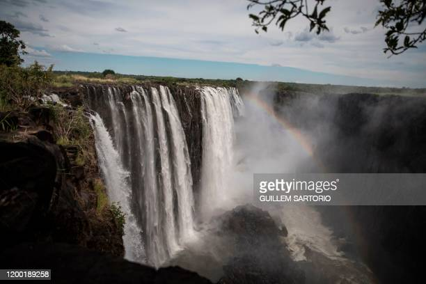 A rainbow emerges at the Victoria Falls in Livingstone on January 23 2020 The Victoria Falls a UNESCO world heritage site measuring 108 meters high...