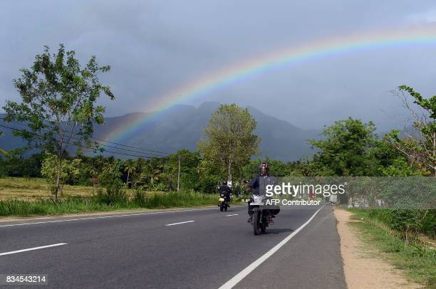 A rainbow falls over a road in Mahiyanganaya near the Mahaweli River in Sri Lanka's Uva Province on August 18 2017 The meteorological phenomenon of...