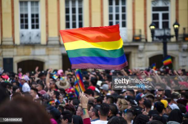 rainbow flag in crowd against building - demonstration stock-fotos und bilder