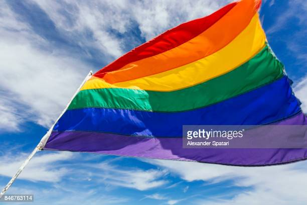 Rainbow flag waiving in the wind against blue sky