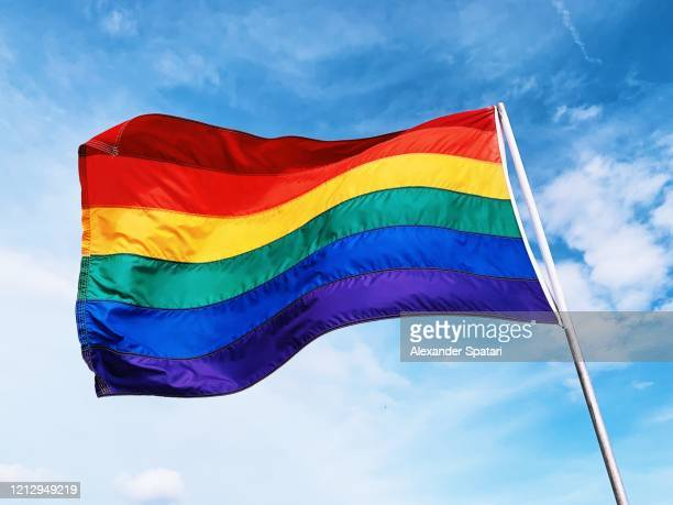 rainbow flag waving in the wind against blue sky - lgbtq stock pictures, royalty-free photos & images