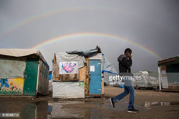 A rainbow forms as a migrant talks on a mobile phone as he walks through the Jungle migrant camp on October 22 2016 in Calais France French...