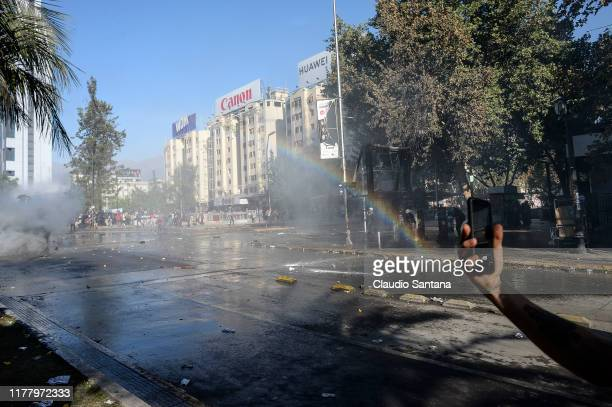 A rainbow forms as demonstrators clash with the police during the seventh day of protests against President Sebastian Piñera on October 24 2019 in...