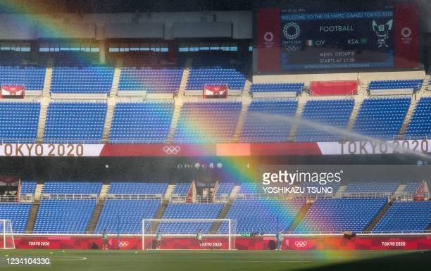 Rainbow forms as sprinklers water the pitch prior to the Tokyo 2020 Olympic Games men's group D first round football match between Ivory Coast and...