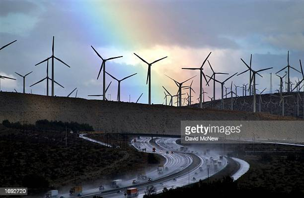 A rainbow forms behind giant windmills near rainsoaked Interstate 10 as an El Ninoinfluenced storm passes over the state on December 17 2002 near...