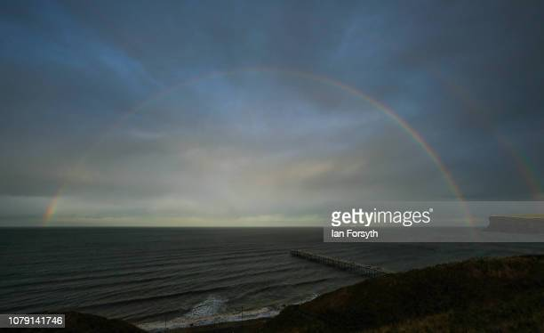 A rainbow forms over the pier and cliffs on December 8 2018 at SaltburnbytheSea England Showers are expected to continue to spread eastwards across...