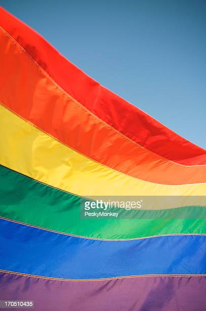 Rainbow Gay Pride Flag Waves in Sun against Blue Sky