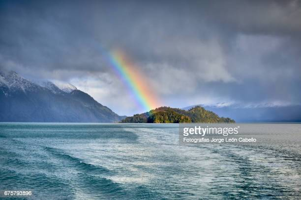 a rainbow glimpse ove the islet in lago todos los santos during the winter andean lake crossing - azul turquesa stockfoto's en -beelden