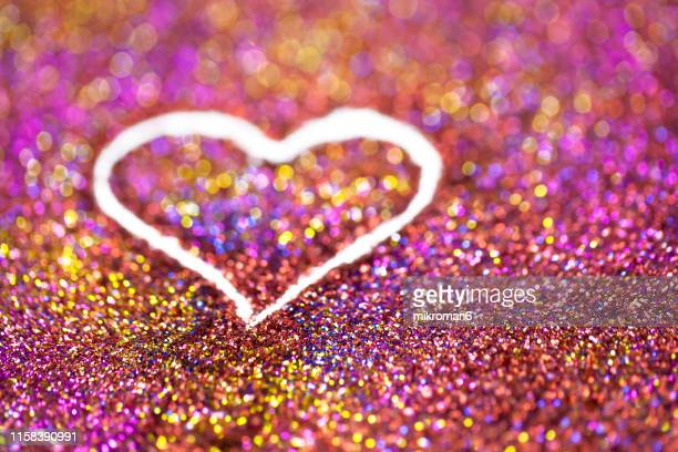 rainbow glitter, heart shape - heart month stock photos and pictures