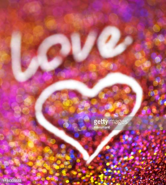 rainbow glitter, love word text and heart - heart month stock photos and pictures