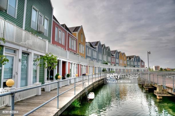 rainbow houses at the pond - houten, the netherlands - utrecht stock-fotos und bilder