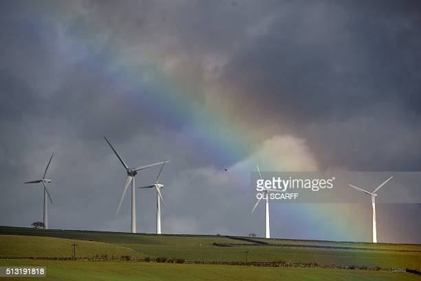A rainbow illuminates the sky above a windfarm in Wortley near Sheffield northern England on March 1 2016 / AFP / OLI SCARFF