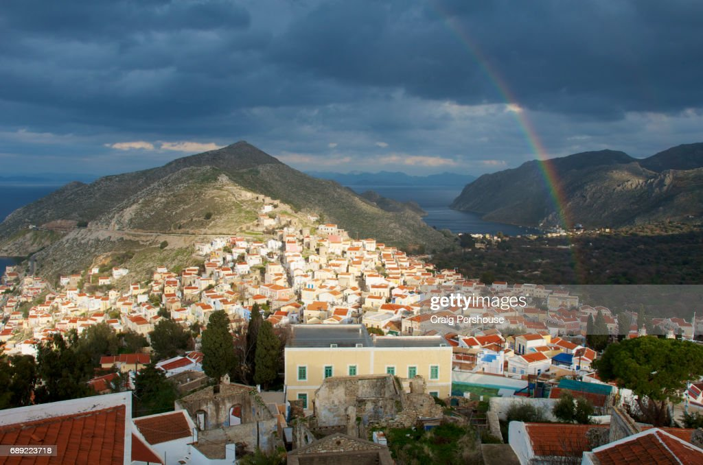 Rainbow in a cloudy sky above the houses of Horio. : Stock Photo