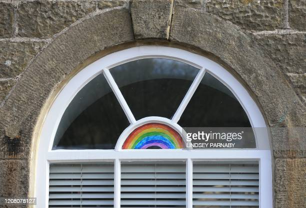 Rainbow in solidarity with coronavirus victims is displayed in a cottage window in the village of Eyam in Derbyshire, northern England on March 23,...