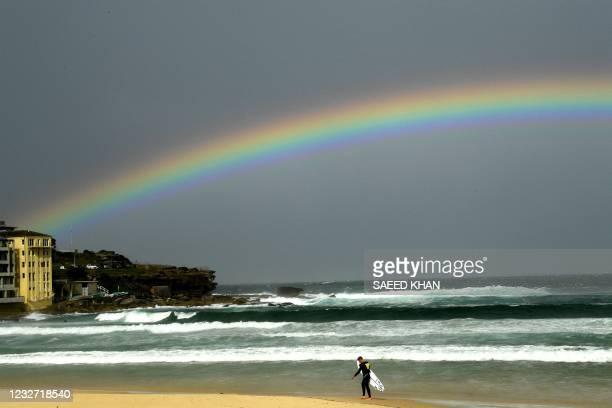 Rainbow is seen as it rains over the Bondi Beach in Sydney on May 6, 2021.