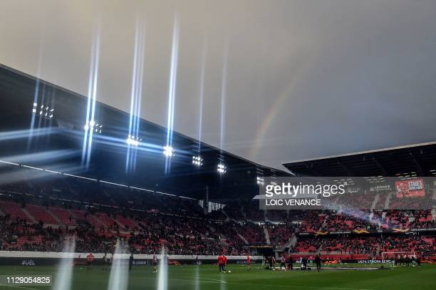 A rainbow is seen as players warm up prior to the UEFA Europa League round of 16 first leg football match between Stade Rennais FC and Arsenal FC at...