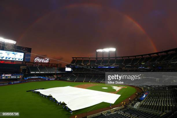 Rainbow is seen as the grounds crew removes the tarp prior to the start of the game between the New York Mets and the Toronto Blue Jays at Citi Field...