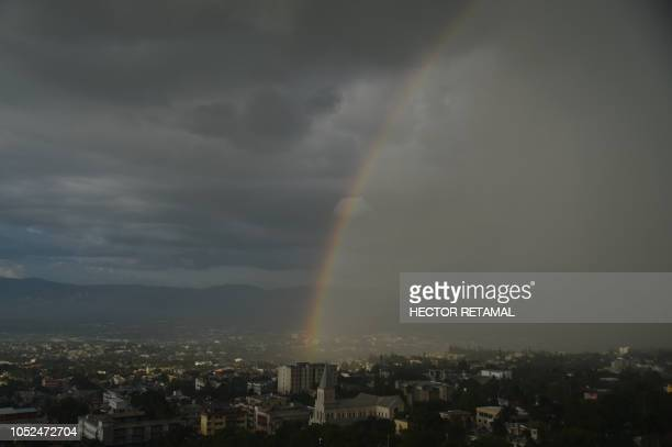 TOPSHOT A rainbow is seen during a sunset rain in the commune of Petion Ville in the Haitian capital of PortauPrince on October 18 2018