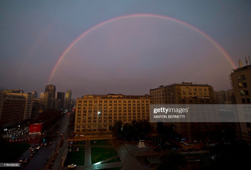 A rainbow is seen in the sky of Santiago de Chile, over Citizenry Square right across La Moneda presidential palace (out of frame), on September 2, 2013.