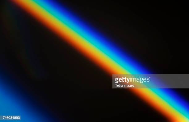 rainbow light against black - rainbow stock pictures, royalty-free photos & images