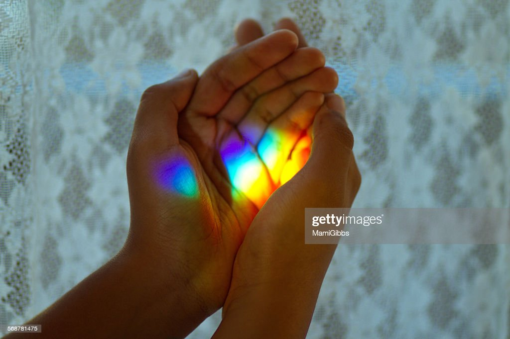 Rainbow light in her hands : Stock Photo