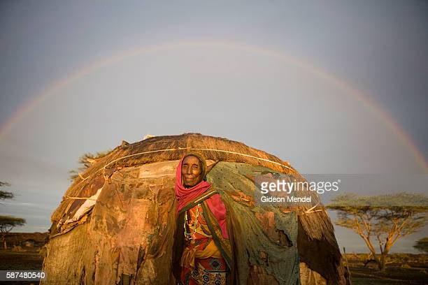 A rainbow looms above 75 year old pastoralist Shake Abudho as she gazes out of her traditional Gabbra shelter in Kalacha This was shortly after one...
