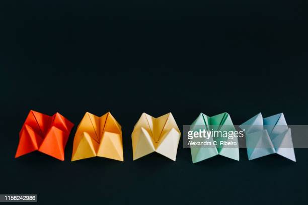rainbow multicolored origami fortune tellers on black background - colors of rainbow in order stock pictures, royalty-free photos & images