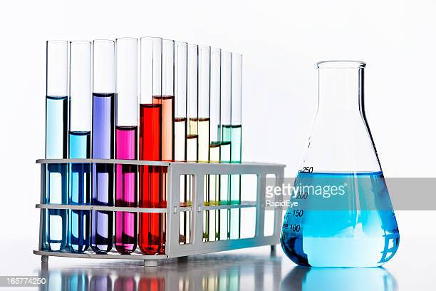 Rainbow of colored liquids, backlit in laboratory glassware