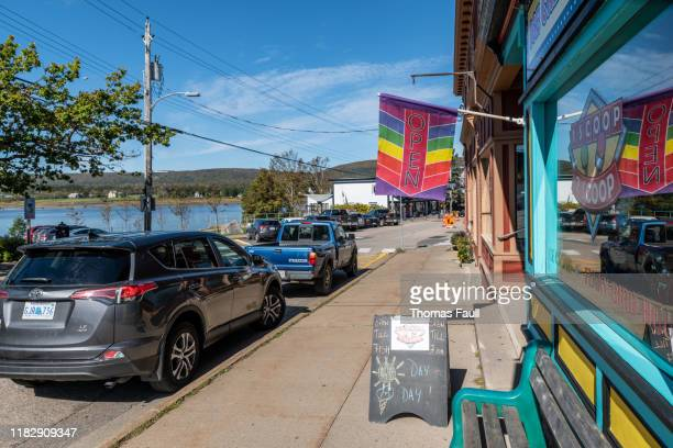 rainbow open flag in the town of annapolis royal, nova scotia - flag of nova scotia stock pictures, royalty-free photos & images