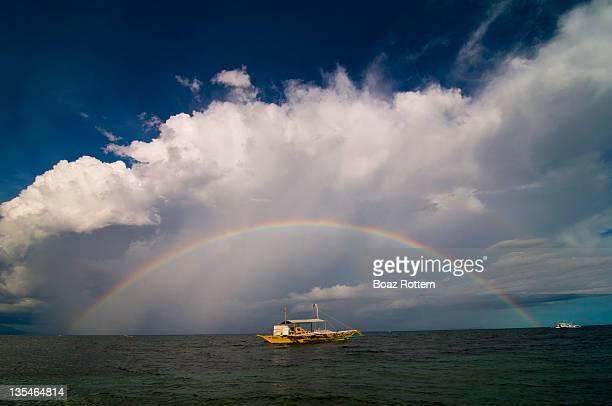 Rainbow over boat in sea