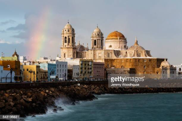 rainbow over domes of ornate cathedral on waterfront, cadiz, andalusia, spain - cádiz fotografías e imágenes de stock