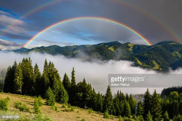 Rainbow over misty mountains in summer morning