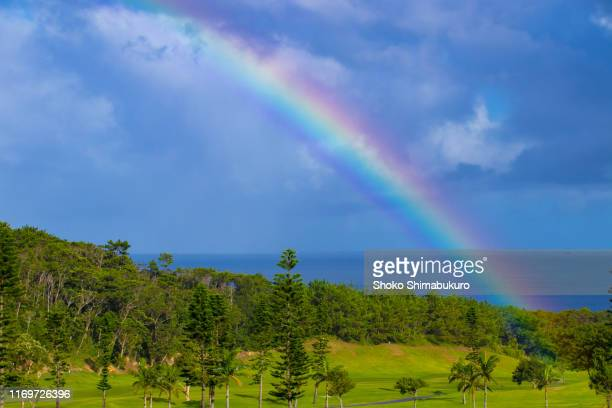 rainbow over the mountain to the sea - rainbow sky stock pictures, royalty-free photos & images