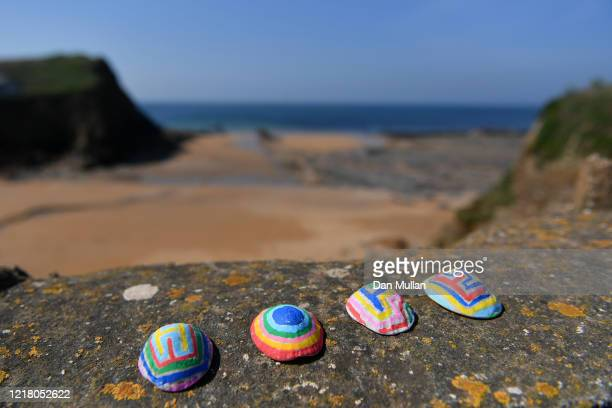 Rainbow painted shells spelling 'HOPE' are displayed on the sea wall of Hope Cove on April 10, 2020 in Hope Cove, England. Public Easter events have...