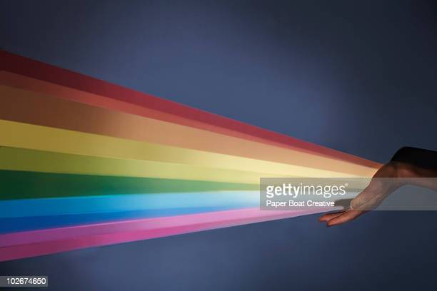 Rainbow projection coming out of woman's hand
