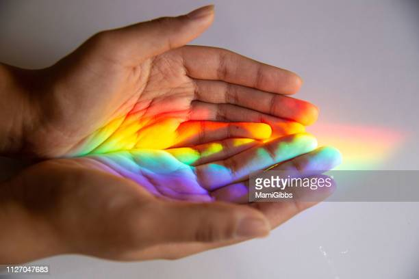rainbow reflected human hands - speranza foto e immagini stock