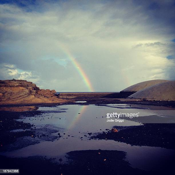 Rainbow reflected in large puddles of water